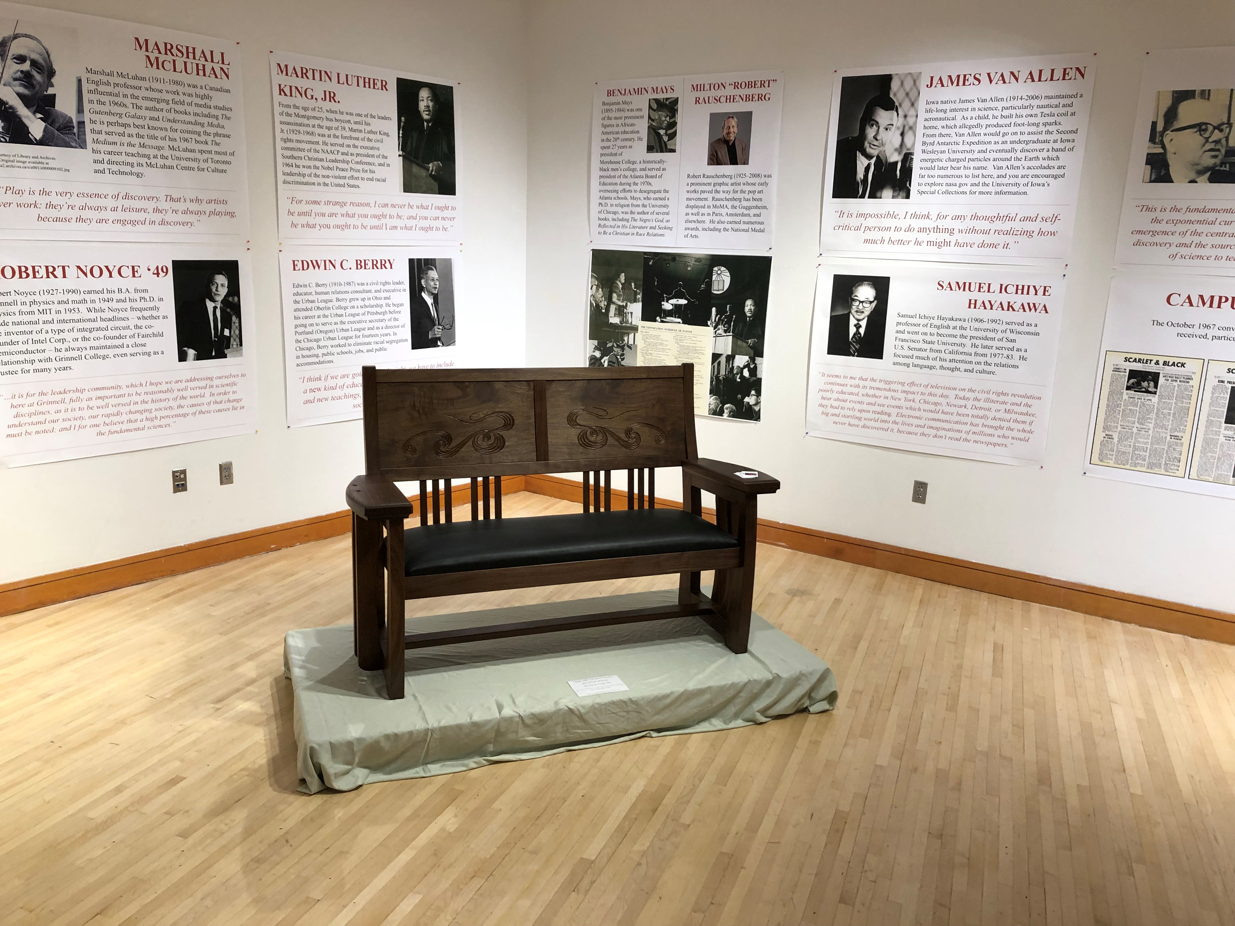 Small walnut bench displayed during 2019 alumni weekend at Grinnell College.